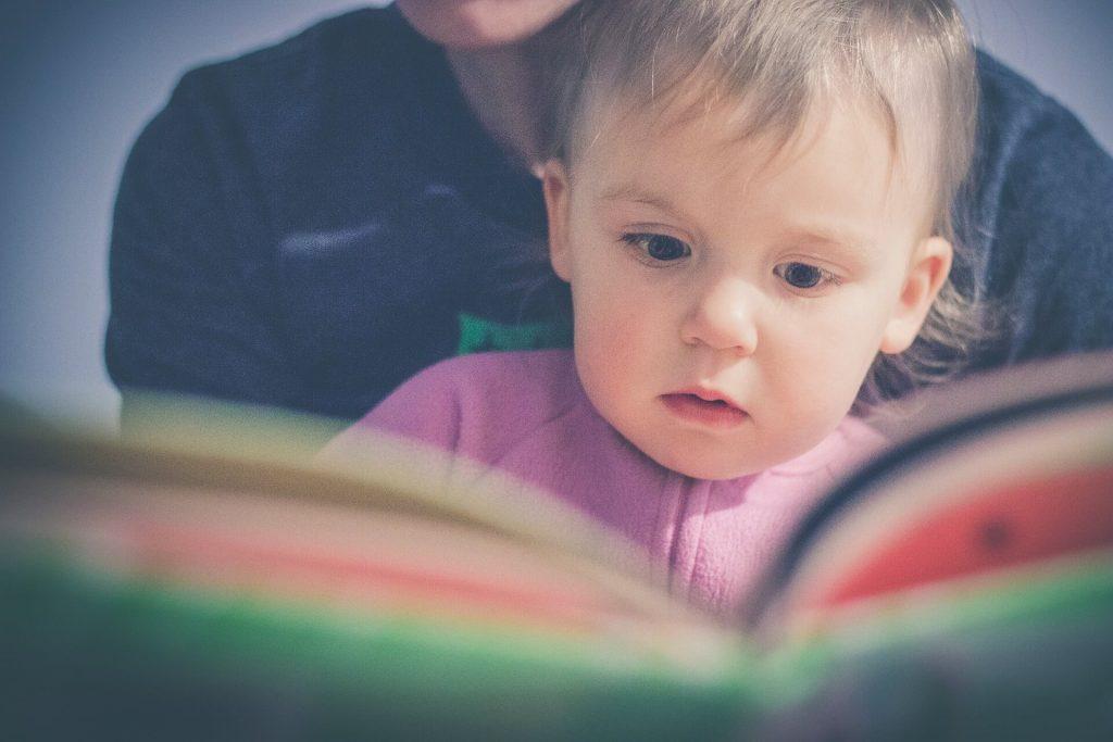 Bebé ojeando un libro con su progenitor