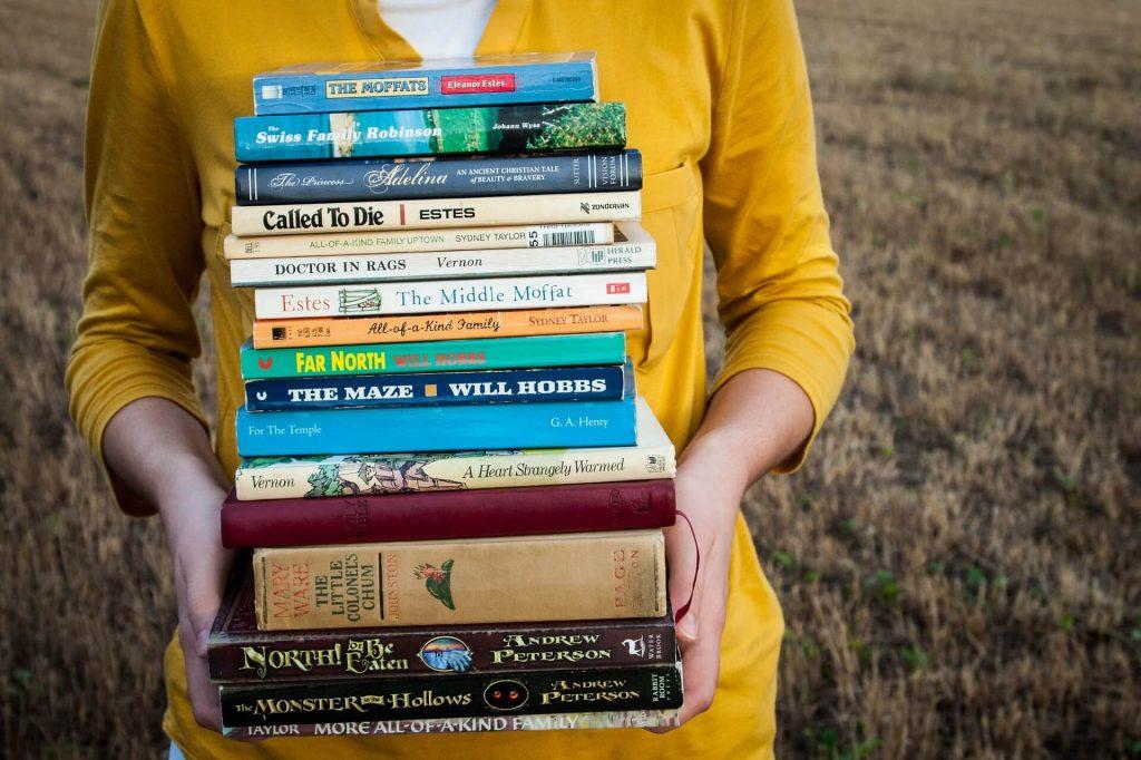 Plano corto de mujer sosteniendo una pila de libros