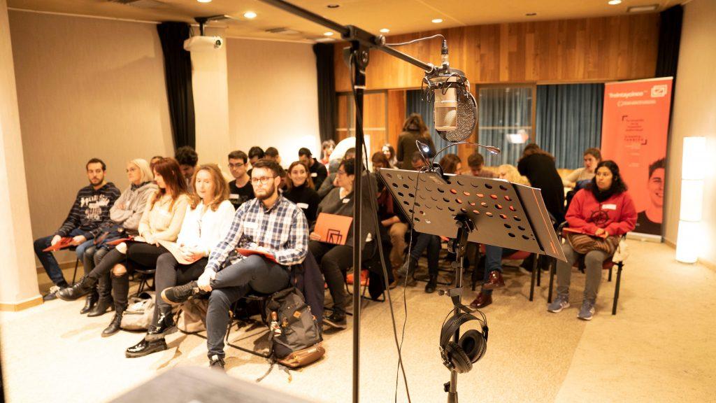 atril, micrófono y, al fondo, asistentes a la masterclass